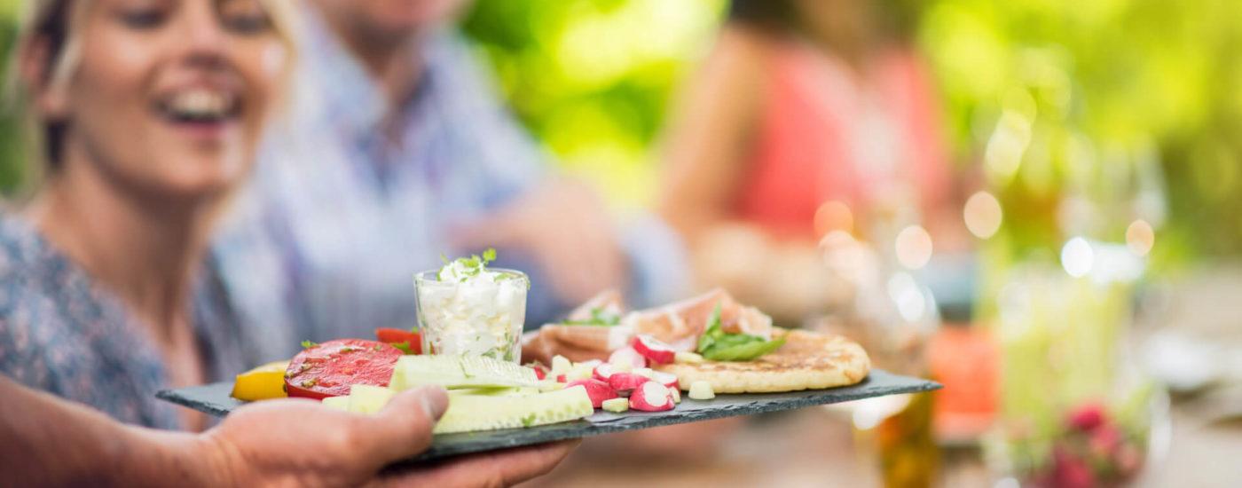 Hand reicht Essensteller ins Bild - Essfit