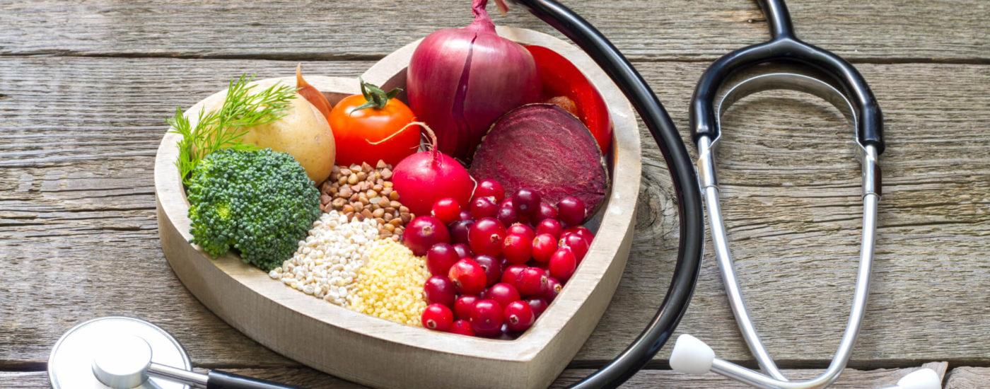 Essen auf herzförmigem Teller mit Stethoskop daneben - Herzgesunde Ernährung Essfit